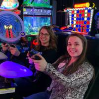 Two alumni smiling before playing arcade game